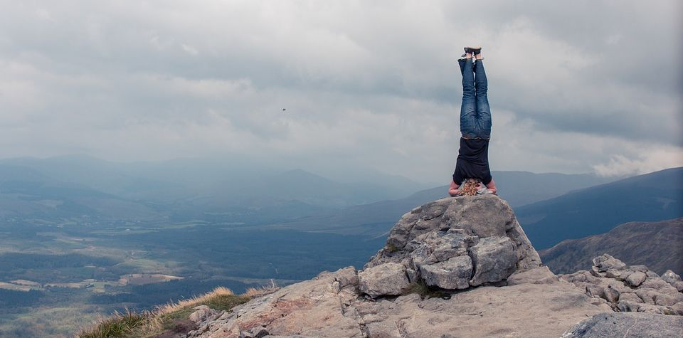 Woman doing headstand pose at top of a stone