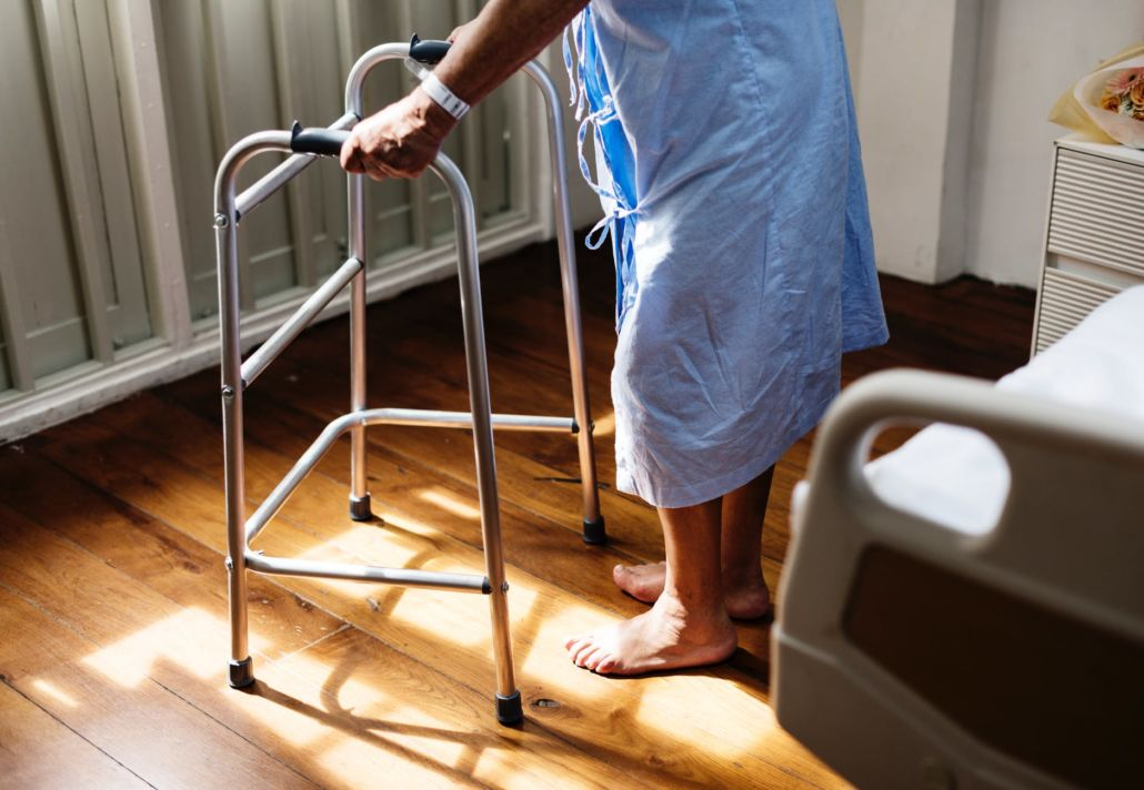 Old woman with walking frame beside hospital bed