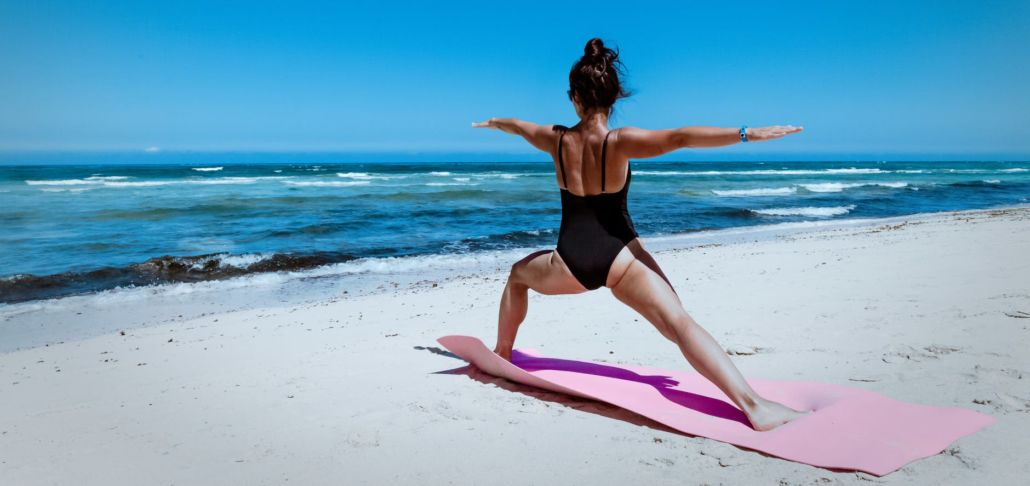 Woman doing yoga at shore