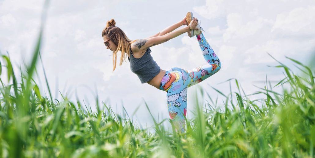 Woman stretching in the middle of grass